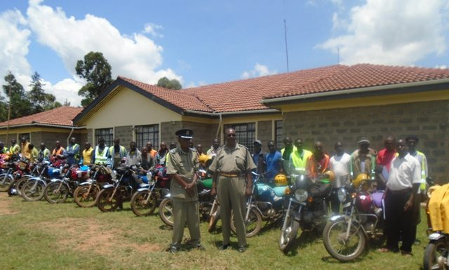 Lugari OCPD Bernard Macharia and driving test examiner Jamal Noor with boda boda cyclists outside Lumakanda Police station before the riding test