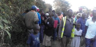 Boda boda riders and villagers milling around the body of a victim who was killed by unknown thugs