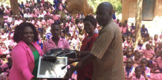 Judy Ojaamong presents a desktop to Akatagoroit Primary School