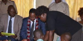 Principal Secretary in the Ministry of Interior and Cordination of National Government Karanja Kibicho centre being taken through one of the tablets at Hambale primary school