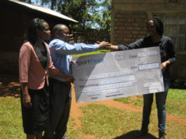 Wafula Munoko receiving his cheque from Laura of SportPesa