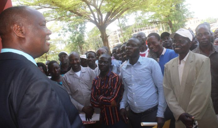 Busia Governor Sospeter Ojaamong addressing farmers outside the county offices
