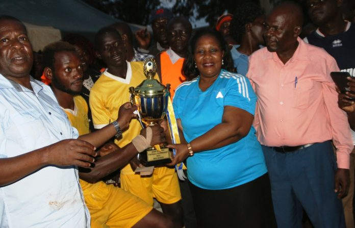 Mama Ni Mmoja soccer tournament sponsor Florence Mutua with Suba MP John Mbandi (left) and ODM Busia County chairman Innocent Oluku with the trophy won by Busia Olympics at Malaba Primary School on Sunday
