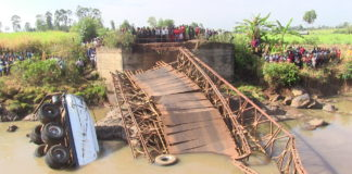 Navakholo residents watch the truck and collapsed bridge after the incident