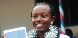 Grace Ekirapa, the top girl in Busia County in 2015 KCSE Exams with an A plain, holding a tablet she received from her school, Kolanya Girls for her exemplary performance