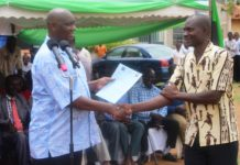 Busia Governor Sospeter Ojaamong presents an appointment letter to an ECDE teacher during the event
