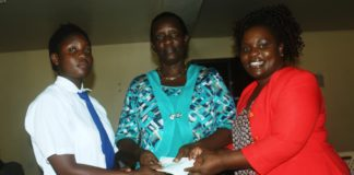 Busia First Lady Judy Ojaamong presents a cheque of Ksh 20, 000 to Busia Girls Secondary School Principal Judith Okanda and Lydia Achieng Owino