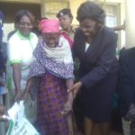 Matulo Ward Administrator Mrs Simuli assists a resident to carry the fertilizer