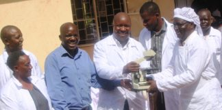 Busia County Executive Committee Member for Agriculture and Animal Resources Dr Moses Osia (Centre) hands over a Microscope to Teso South Meat Inspector Dr Polycarp  Kundembule