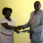 NACADA Regional managerfor Nyanza and Western Region Esther Okenye presents a copy ofthe report on Alcohol and Drug Abuse baseline survey in Busia County to Deputy Governor Kizito Wangalwa at Busia ATC