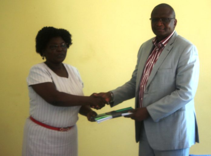 NACADA Regional manager for Nyanza and Western Region Esther Okenye presents a copy of  the report on Alcohol and Drug Abuse baseline survey in Busia County to Deputy Governor Kizito Wangalwa at Busia ATC