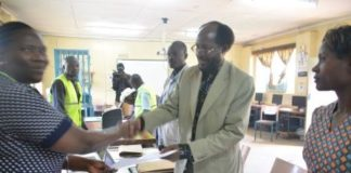 An aspirant being handed a certificate by Vihiga County returning officer Mrs. Sarah Ogaro at Chavakali High School
