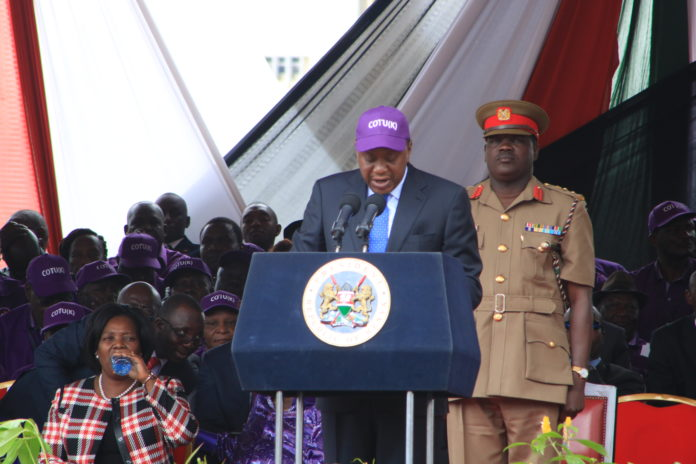President Uhuru Kenyatta addressing listeners during Labour Day celebrations at Uhuru Park on Monday