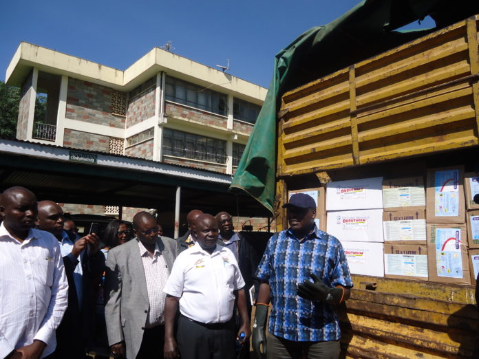 Livestock Principal Secretary Dr Andrew Tuimur at the Nandi County head offices handing over the pesticides