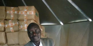 Kimilili Deputy County Commissioner Reuben Loyotoman displaying some of the flour they impounded