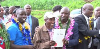 Agriculture Cabinet Secretary Willy Bett handing over title deeds to Setek residents in Nandi County