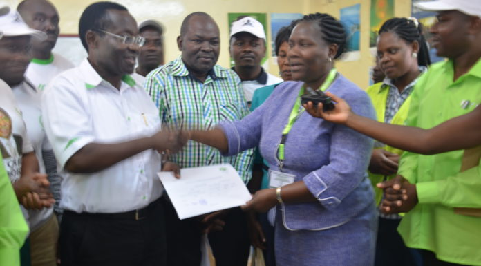IEBC Vihiga County Returning Officer Sarah Ogalo handing over the nomination Certificate to Vihiga Constituency member of parliament Yusuf Chanzu at Chavakali High School in a past function