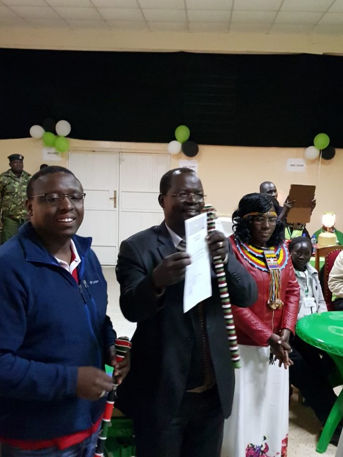Governor elect Prof John Lonyangapuo being given his certificate after the just concluded polls