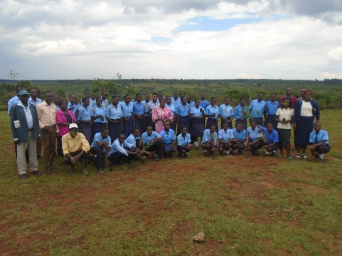 Lugari Sub County Foresters Association officials, teachers, and students of Sipande secondary school during a tree planting exercise