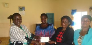 Lugari DCC Mrs. Agnes Shadrack handing over cheques to beneficiaries
