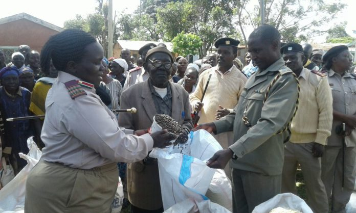 Lugari Deputy County Commissioner Mrs. Agnes Karoki Shadrack on the left with Deputy OCPD Mr. Anthony Njeru giving the relief food to the elders