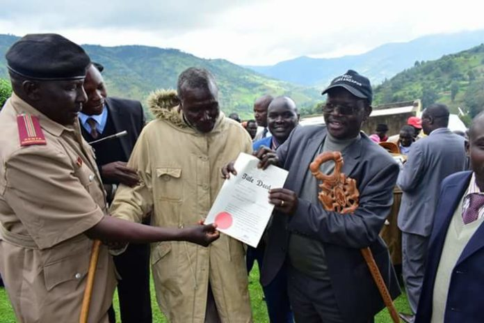 West Pokot Governor John Lonyangapuo (right) issuing the title deeds