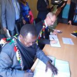 West Pokot Governor John Lonyangapuo and US Ambassador Bob Godec signing an MoU