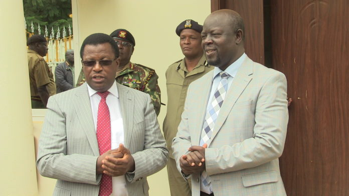 National Police Service Chairman Johnstone Kavuludi (left) with Trans Nzoia Governor Patrick Khaemba (right) in Kitale at the Trans Nzoia County headquarters