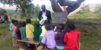 Pupils taking their class under a tree