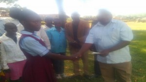 a beneficiary receiving a cheque from Malava education fund chair Juma  Shitiavi/ Photo /Brendah Wawire/ West Fm