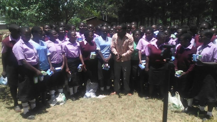 Peter Nabulindo the well wisher posing for a photo with the students  from St. Marys Namalasire girl's secondary school