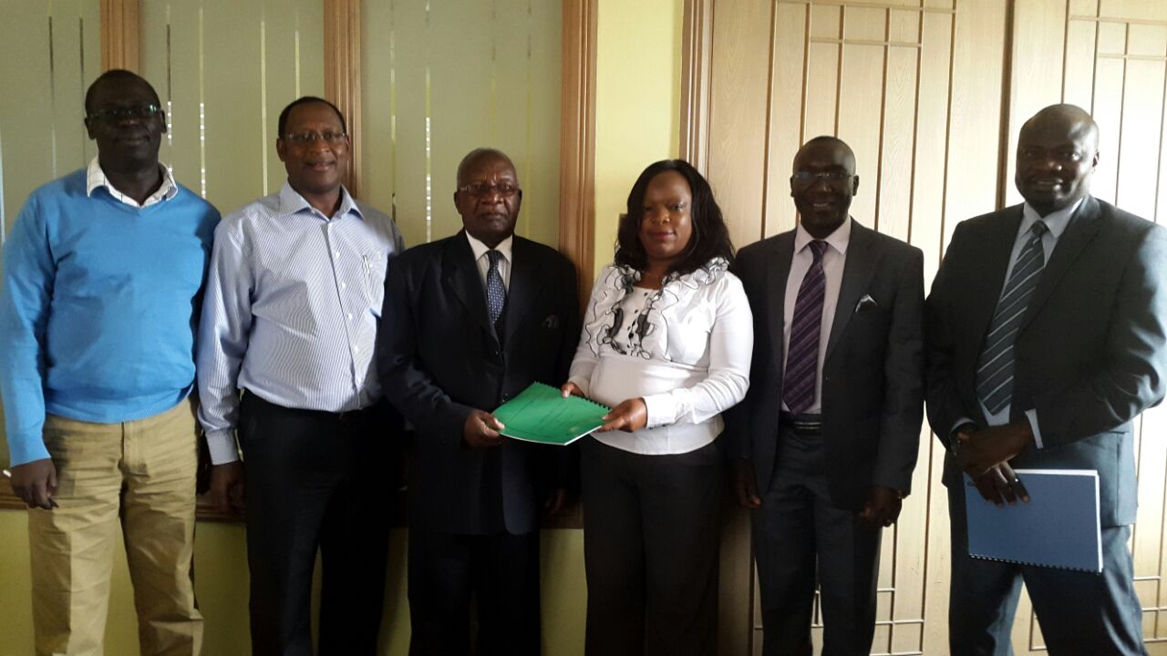 :  Legal Advisor to Busia Governor Sospeter Ojaamong, Justice Alex Etyang exchange the agreement with KPLC Manager Corporate Affairs Beatrice Meso. Looking on is Busia CEC for Roads and Public Works Bernard Yaite (second right) and Chief of Staff Robert Papa (right)