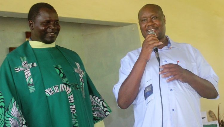 Busia Governor Sospeter Ojaamong addressing worshippers at Mundika Catholic Church flanked by Fr. Maurice Langiri.