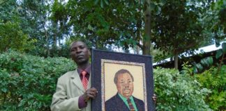 Mr. Joseph Shilesi showing a portrait of COTU Secretary General Francis Atwoli