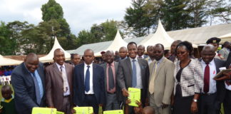 Goibem Standard One kids, alongside Lands CS Jacob Kaimenyi, displaying their laptops during the launch of the Program