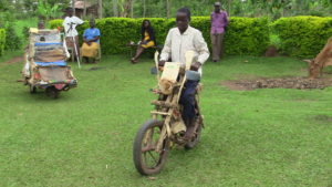 Muchilwa riding his wooden motorcycle