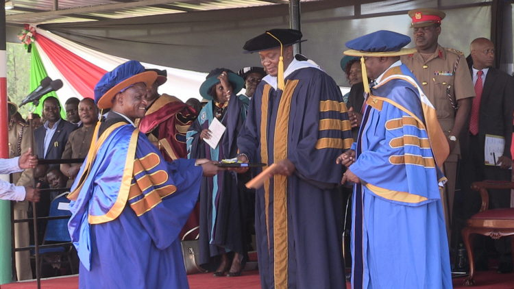 President Kenyatta handing over a doctorate degree to the only doctorate graduate during Kibabii University graduation ceremony