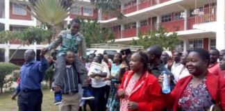 Eugene Asava hoisted by parents and teachers at the school compound