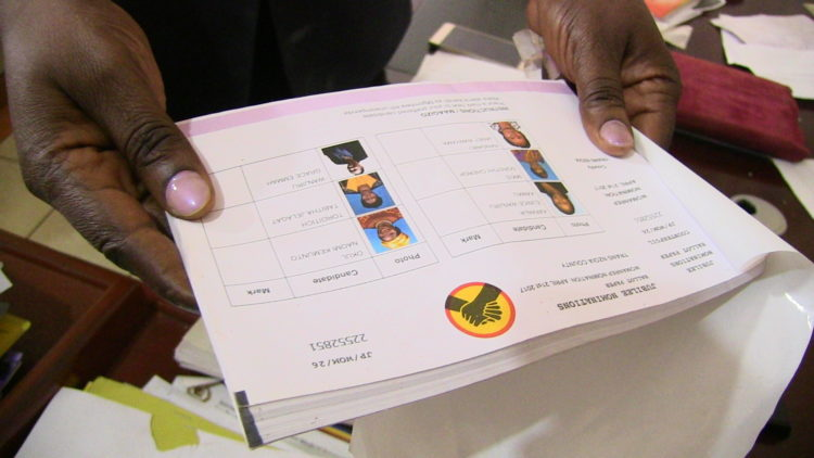 The police commander flipping through the pages of the Jubilee elections booklets that were recovered