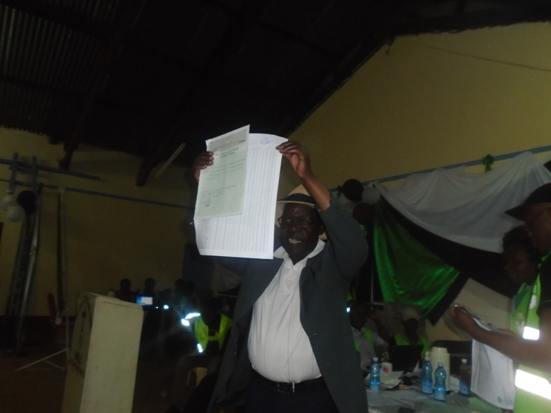 Likuyani MP elect Enoch Kibunguchyshowing the certificate to his supporters