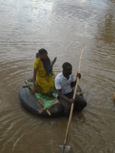 A woman crossing river Nzoia on a motor vehicle tube