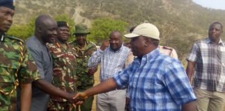 Interior CS Fred Matiang'i is welcomed by former West Pokot Governor and Education CAS Simon Kachapin during a past visit to the region. FILE
