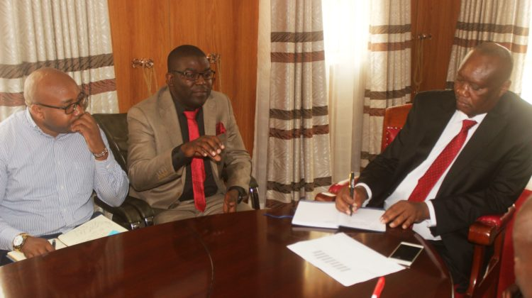 Busia Governor Sospeter Ojaamong, ANPPCAN DirectorAggrey Otieno and Program OfficerEvans Munga (left) in his office