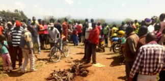 Residents look at the wreckage of the motorbike involved in the accident in Amukura, Teso South