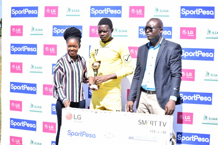 Amos Kigadi (centre) receiving his dummy cheque of Kshs 100,000