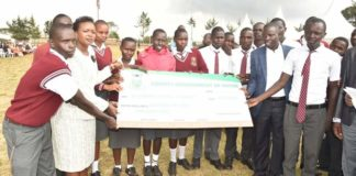 Nandi Governor Stephen Sang giving out County bursary cheques to students at Kapkoimur in Mosop constituency