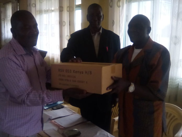 The Friends Church Kenya presiding clerk Henry Mukwanja handing over the Bibles to the Church National Educational secretary Ben Nasikungu (left)