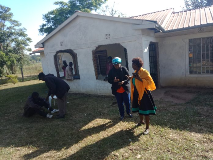 Family members console each other outside police officer Corporal Edwin Wasike's house