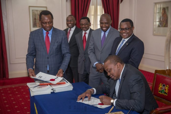 President Kenyatta signing the three Bills into law at State House. (Photo/Pscu)