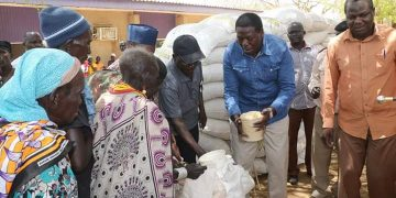 Devolution CS Eugene Wamalwa (in blue) during the food distribution exercise